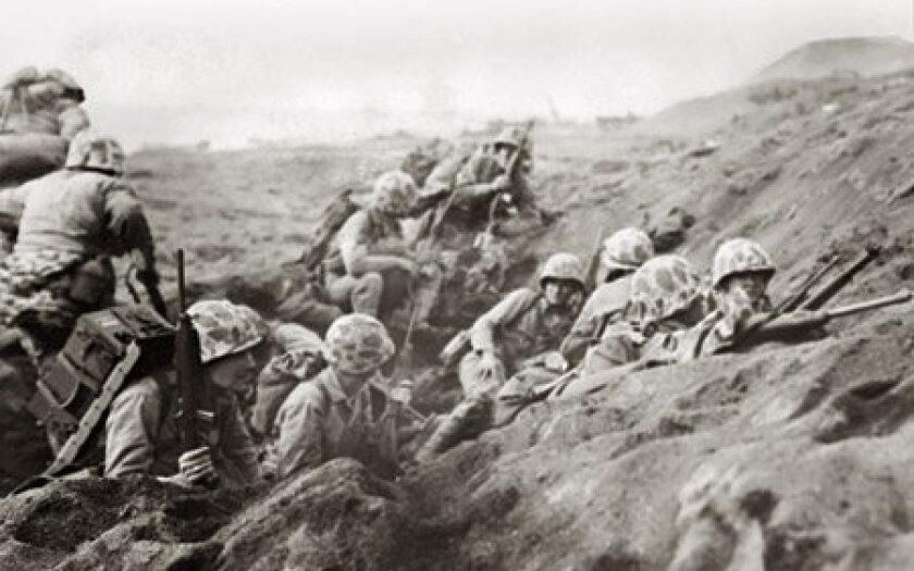 U.S. Marines, pinned down by Japanese fire, took shelter on the first terrace above the beach of Iwo Jima on Feb. 27, 1945. (U.S. Marine Corps)