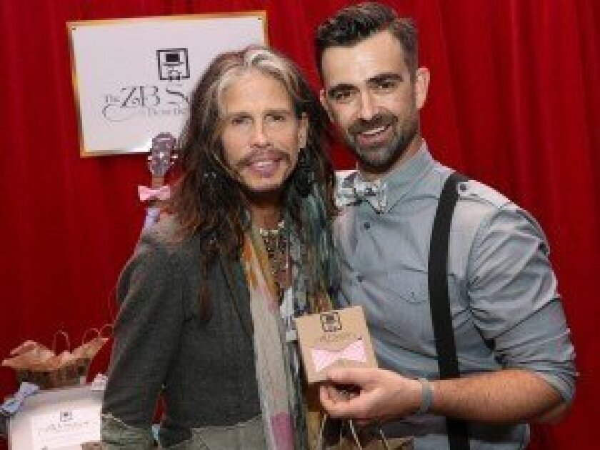 Zach 'ZB' Barnhorst (right) gives one of his bow ties to Aerosmith vocalist and former 'American Idol' judge Steven Tyler at a Grammy Awards 'gifting suite' in January. Photo by Imeh Akpanudosen/WireImage