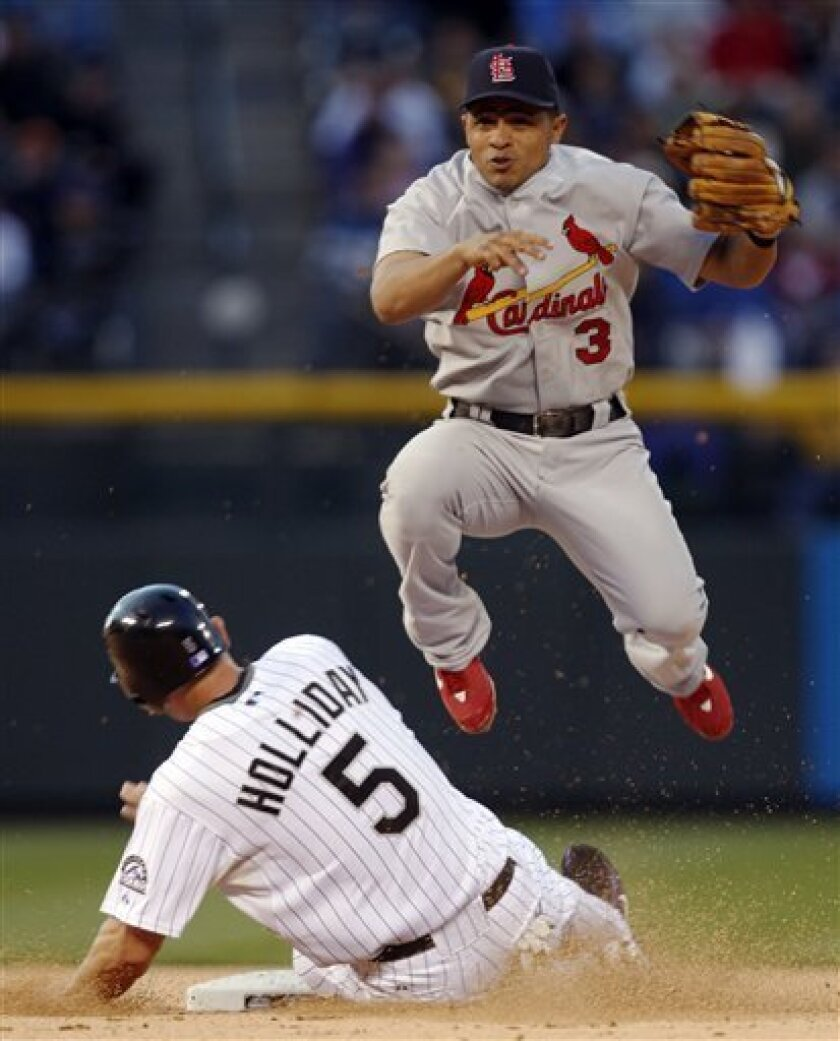 St. Louis Cardinals shortstop Cesar Izturis, top, hops over Colorado Rockies' Matt Holliday after forcing him out at second base on the front end of a double play hit into by Todd Helton in the fourth inning of a baseball game in Denver on Wednesday, May 7, 2008. (AP Photo/David Zalubowski)