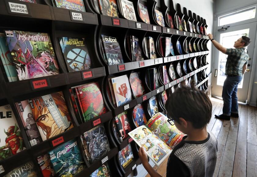 A boy looks at a comic book at Secret Headquarters.