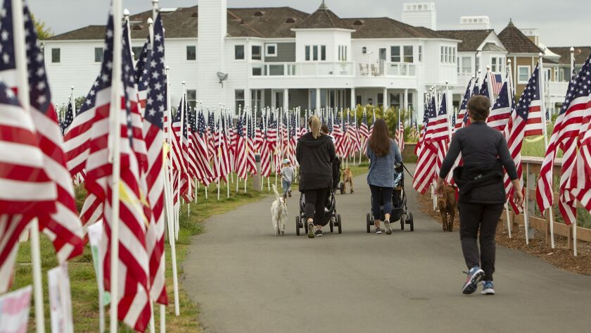 Morning walkers stroll through the Field of Honor, filled with 1,776 US flags, at Castaways Park in