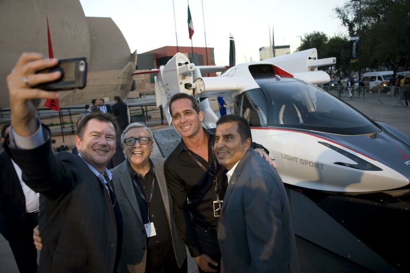 Kirk Hawkins, (second from right), CEO and Founder of ICON Aircraft poses for a photograph in front of the company's A5 aircraft, during a presentation in Tijuana, Mexico, on September 8, 2016. ICON Aircraft will begin to produce composite airframe components in Tijuana this November. L-R are Charl
