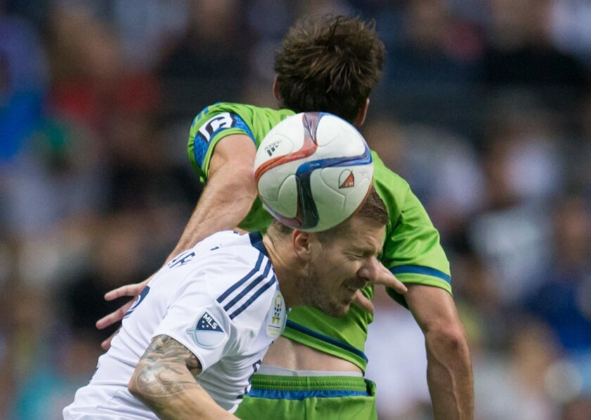 Vancouver Whitecaps' Jordan Harvey and Seattle Sounders' Brad Evans, back, vie for the ball during the first half of an MLS soccer game in Vancouver, British Columbia, on Saturday, Sept. 19, 2015. (Darryl Dyck/The Canadian Press via AP)