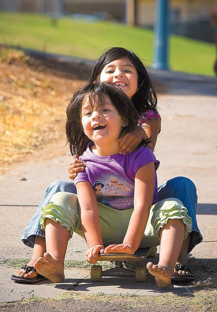 Vivian Lopez (front) and sister Brianna rode on a skateboard yesterday near  their home in San Diego's Grant Hill neighborhood. (Nelvin C. Cepeda / Union-Tribune)