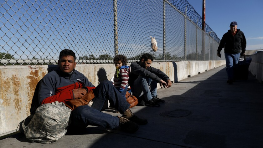 Asylum seekers Elvis Gonzalez Rodriguez, 23, left, of Havana and Robert Richard Braganca of Rio de Janeiro, with his toddler son, Mario, wait on the Matamoros and Brownsville International Bridge in Matamoros, Mexico.
