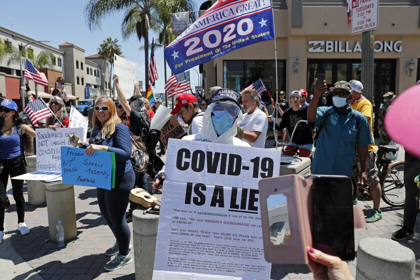 Demonstrators crowd the intersection at Main Street and Walnut Avenue in downtown Huntington Beach on Friday to protest against social distancing and the economic shutdown.