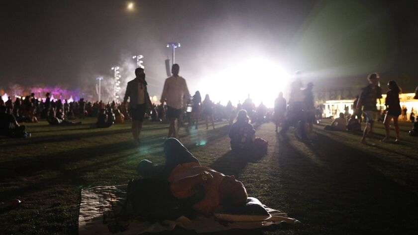 INDIO-CA-APRIL 21, 2018: A man sleeps while Beyonce performs, in background, at Coachella Weekend 2