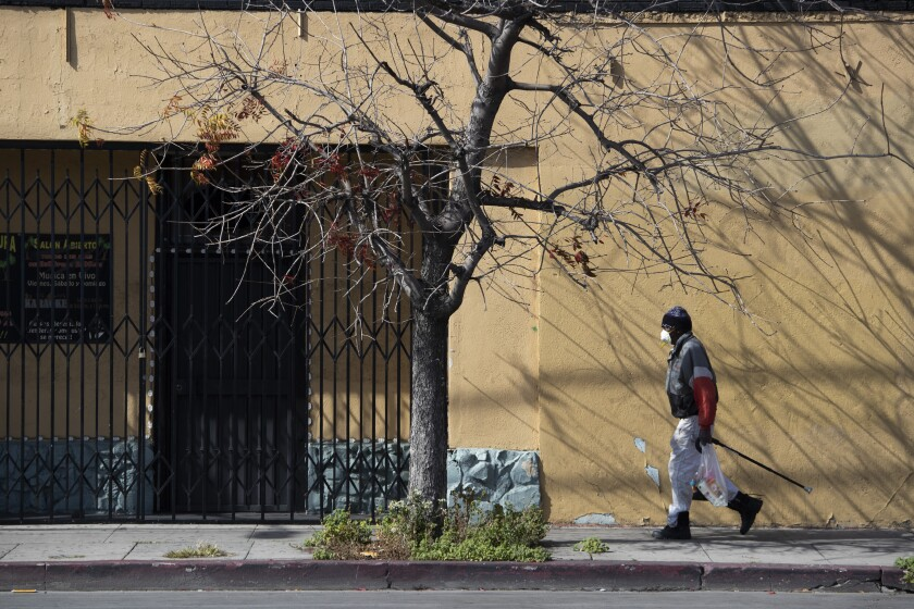 A man carries groceries past the shuttered Beylul Restaurant on Saturday, April 4, 2020 in West Adams, CA.