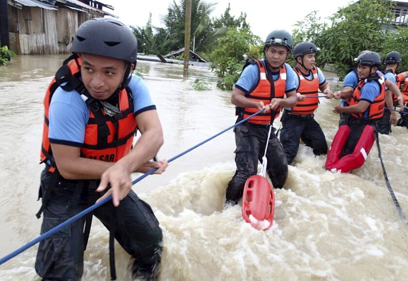 In this Sunday, Jan. 12, 2014 photo, rescuers from the Comval Emergency Response Team continue their rescue operation following the flooding of Compostela Valley and nearby provinces in southern Philippines. Floods and landslides triggered by heavy rains from a low pressure area affected 132,000 people from 10 provinces but it was still unclear how many of them had to evacuate their homes, disaster response officials said Monday, Jan. 13, 2014. (AP Photo/A. Dayao)