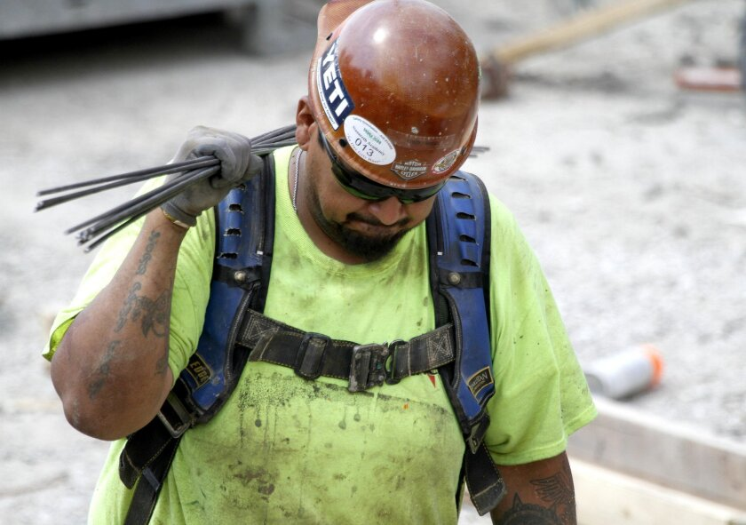 A construction worker carries rebar through a luxury apartment site during the heat of the day, Wednesday, July 20, 2016, in Chicago. The Occupational Safety and Health Administration urged employers to protect laborers doing construction, road and agricultural work, as high temperatures and humidi