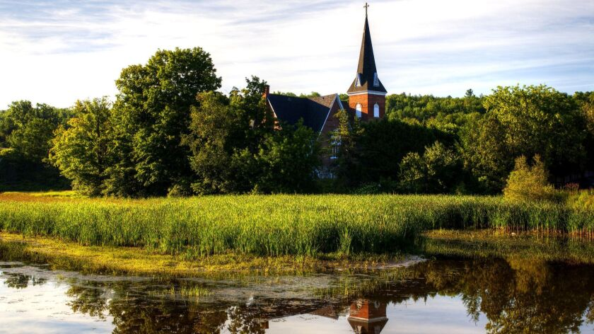 The United Church is reflected in a pond in Knowlton, Canada, a village in Quebec's Eastern Townships that stands in as Three Pines in Louise Penny's books.