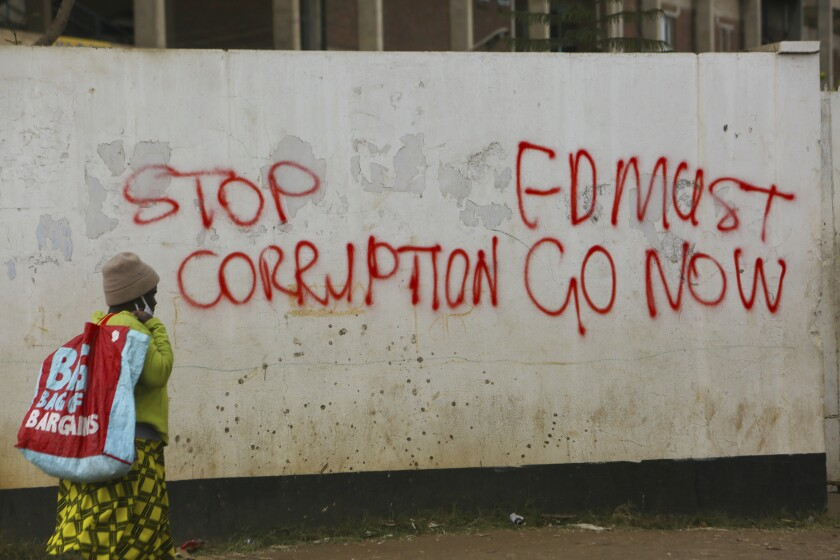 A woman walks past a wall with graffiti calling on the government to stop corruption.