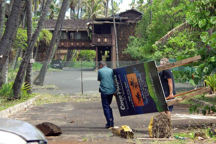 """FILE - In this Sept. 13, 2007, file photo, workers move the Coco Palms Resort unit sales sign away from the Kuamoo Road side of the former resort in Wailua, Hawaii. The historic resort where Elvis Presley's character got married in the 1961 film """"Blue Hawaii"""" will go up for auction at a foreclosure sale on Kauai this month. The Garden Island newspaper reported the abandoned Coco Palms Resort will be auctioned July 26, 2021, on the steps of the Fifth Circuit Courthouse in Lihue. (Dennis Fujimoto/The Garden Island via AP, File)"""
