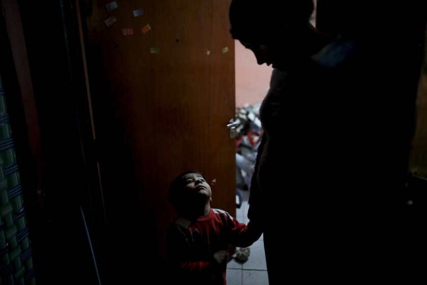 In this June 2, 2020 photo, Valentin Benitez tries to get the attention of his mother Natividad Benitez during an interview in their home, during a government-ordered lockdown to curb the spread of the new coronavirus, in the Villa 1-11-14 slum of Buenos Aires, Argentina. The number of Argentines in poverty is supposed to reach 45 percent this year as the COVID-19 pandemic worsens an already grave economic crisis. (AP Photo/Natacha Pisarenko)