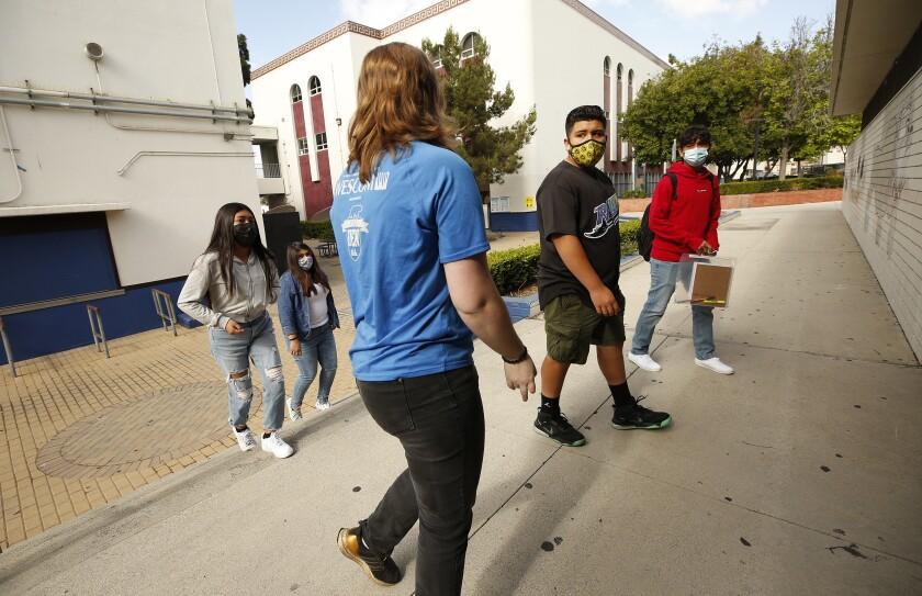 Math and computer science teacher Kelly Flood walks her freshman students around the James A. Garfield High School campus
