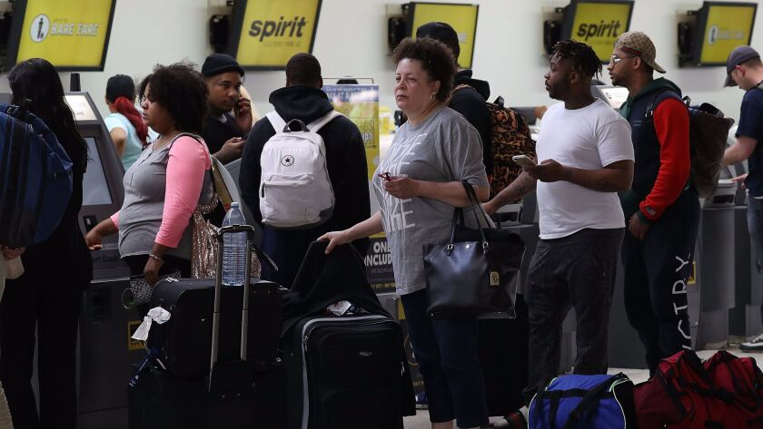 FORT LAUDERDALE, FL - MAY 09: People stand in line to check in at the Spirt Airlines counter at the
