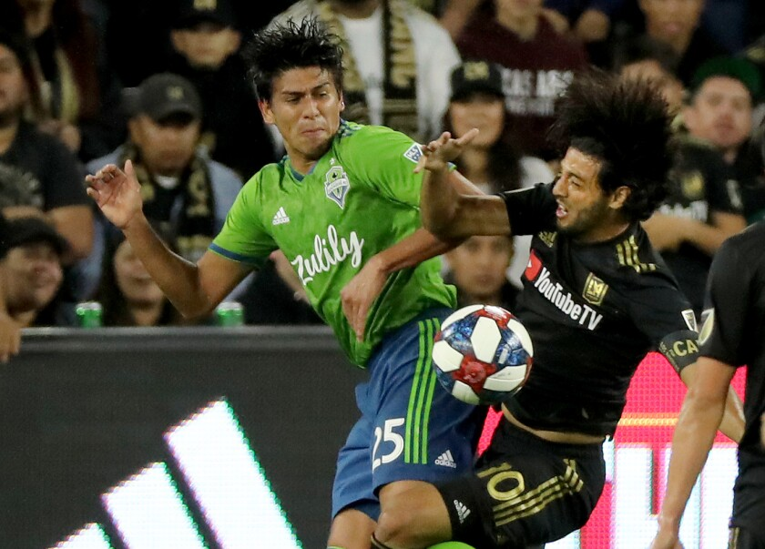 LAFC star Carlos Vela, right, battles Seattle's Xavier Arreaga for control of the ball.