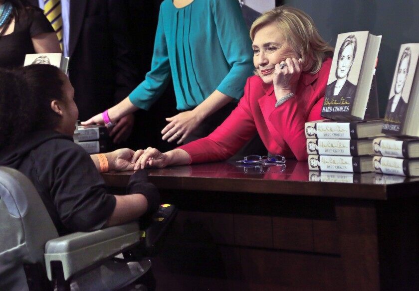 Hillary Rodham Clinton listens before signing a copy of her new book for a woman Tuesday at Barnes and Noble bookstore in New York.