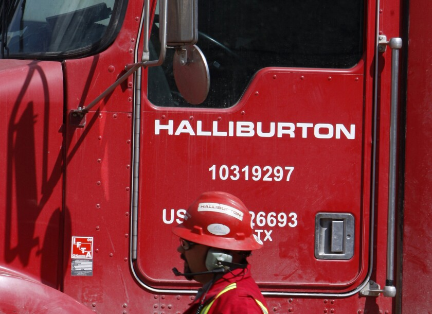 A worker passes a Halliburton truck in Rulison, Colo., in 2009.