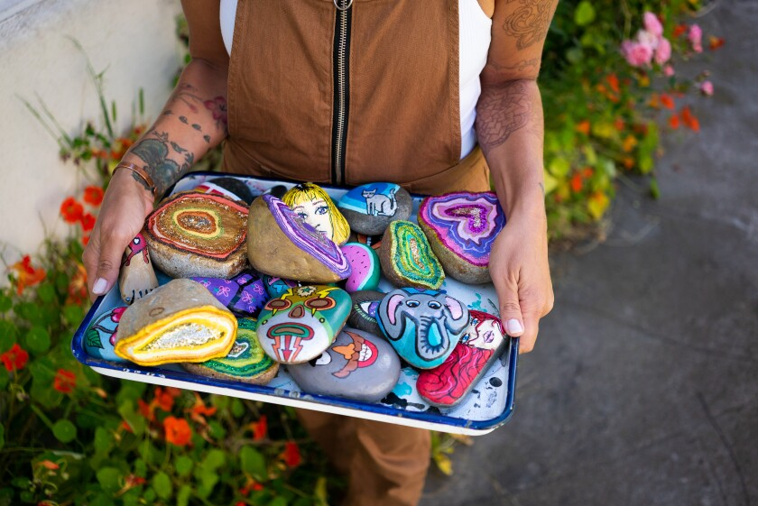 Mary Claire shows off a tray of her painted rocks in her front yard in Pacific Beach. Since the stay-at-home restrictions began, she has been painting rocks and placing them in yards around the neighborhood for people to find in hopes to spread happiness.
