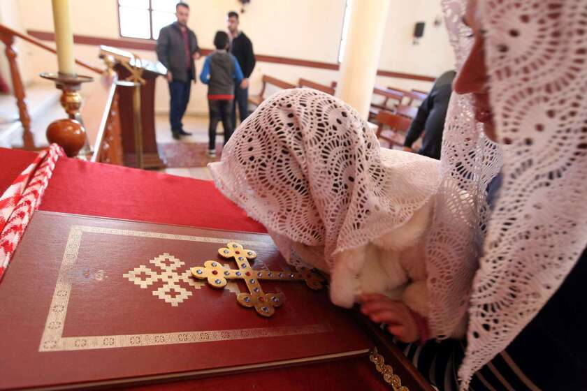 An Assyrian Christian woman and her daughter, who had fled the unrest in Syria, attend a prayer at the St.Georges Assyrian Church in Jdeideh, northeast of Beirut, for the Assyrian Christians abducted by Islamic State militants from villages in northeastern Syria.