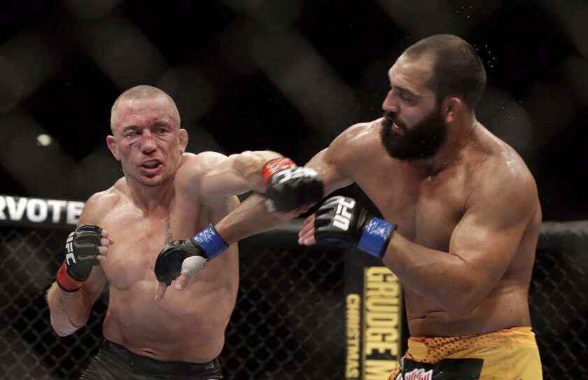 Georges St-Pierre, left, punches Johny Hendricks during UFC 167 on Nov. 19, 2013.