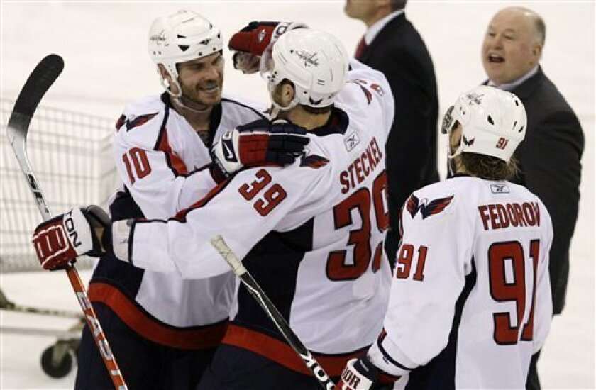 Washington Capitals' David Steckel (39) celebrates his overtime goal against the Pittsburgh Penguins with teammates Matt Bradley (10), Sergei Fedorov (91) of Russia, and coach Bruce Boudreau, right rear, in Game 6 of an NHL hockey second-round playoff series, in Pittsburgh on Monday, May 11, 2009. The Capitals won 5-4. (AP Photo/Gene J. Puskar)