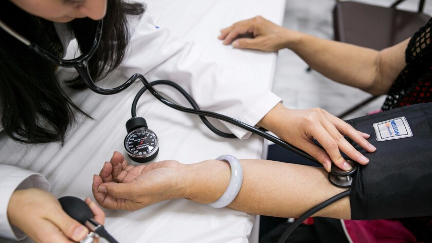 A physician checks a patient's blood pressure. A new study finds that a doctor's political views may influence the care he or she provides, especially when it comes to politically sensitive health issues such as abortion, marijuana use and firearm possession.