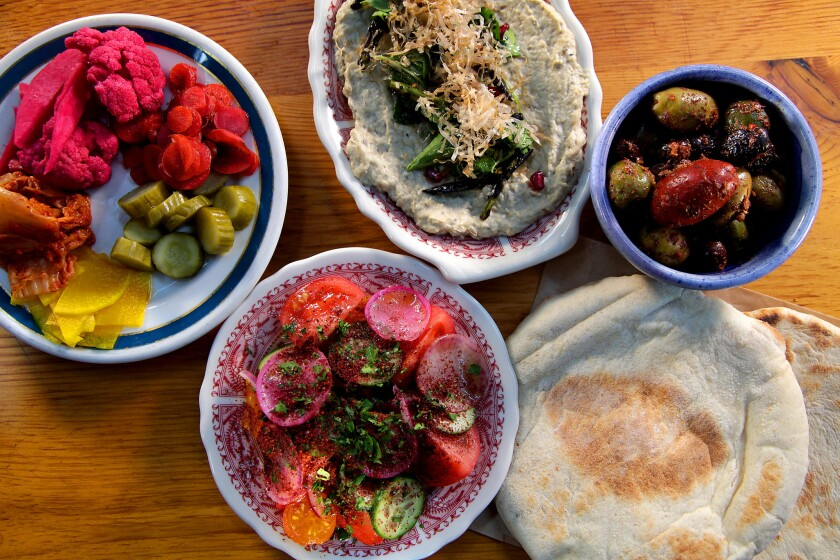 A seasonal plate of pickled and fermented vegetables, plus olives, Arabic salad, burnt eggplant and pita bread.