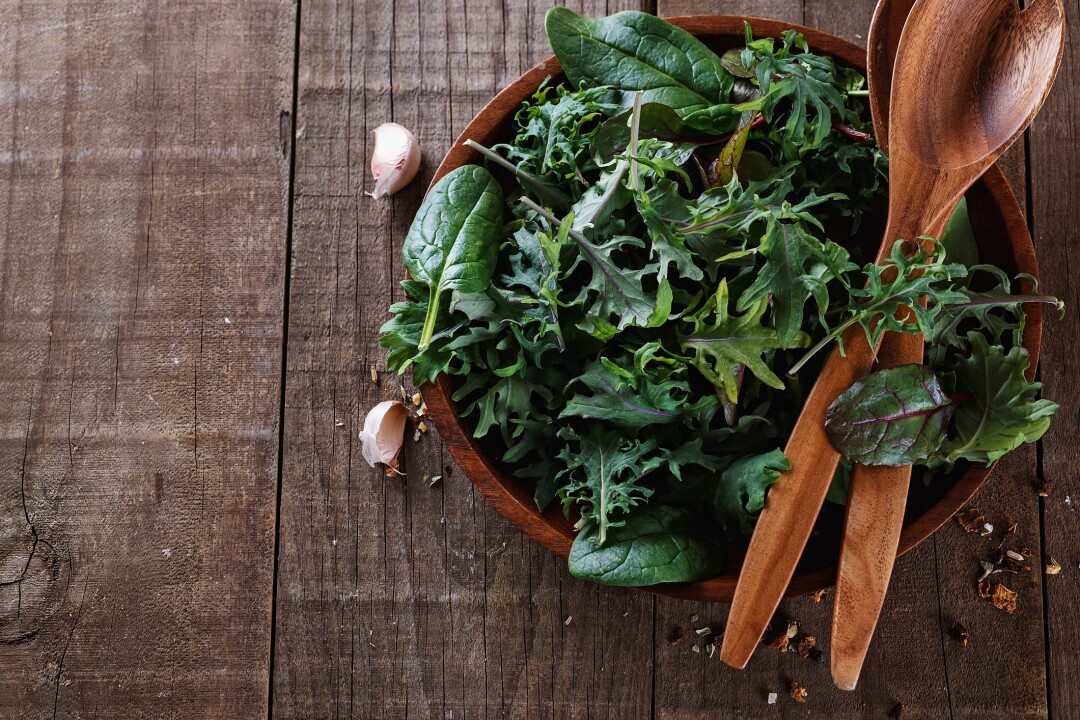 Top view image of leafy green mix over wooden background