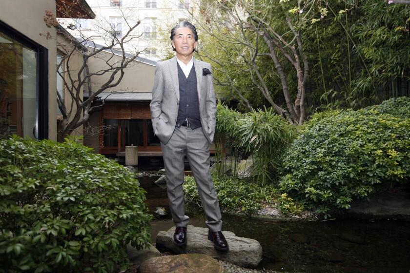 Japanese fashion designer Kenzo Takada poses outside his Paris house
