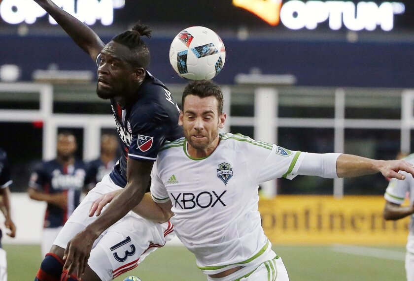 New England Revolution's Kei Kamara (13) battles Seattle Sounders's Zach Scott for the ball during the first half of an MLS soccer game, Saturday, May 28, 2016, in Foxborough, Mass. (AP Photo/Michael Dwyer)