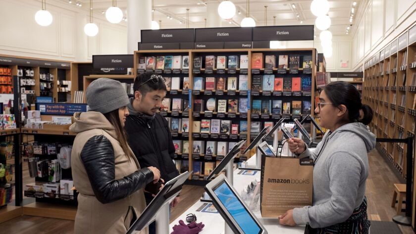 Customers buy a bag of books at an Amazon Books store, Monday, Nov. 20, 2017, in New York. Amazon go