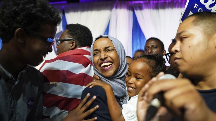 Minnesota state Rep. Ilhan Omar celebrates with her children after her primary victory in August. She'll become one of the first Muslim women in Congress if she wins in Tuesday's election.