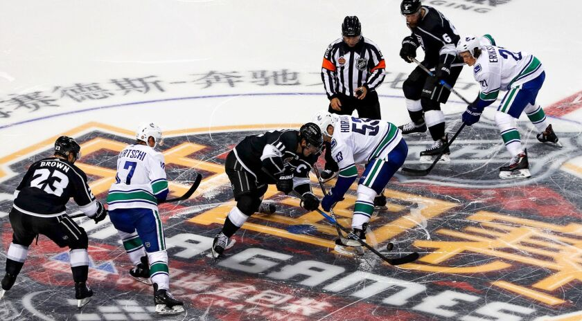 The Kings and Canucks fight for the puck during a preseason game at Mercedes-Benz Arena in Shanghai on Sept. 21, 2017.