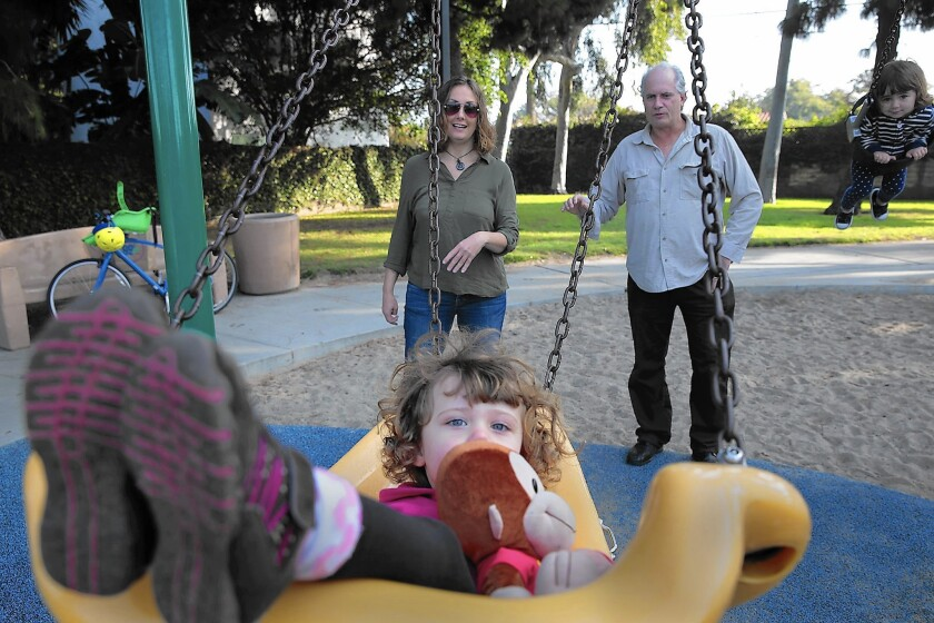 Vanessa Leddy, 2, swings as parents Christy Lambertson, left, and John Leddy watch at Culver West Park. The family decided against a child-care center in Santa Monica because of its low measles vaccination rate.