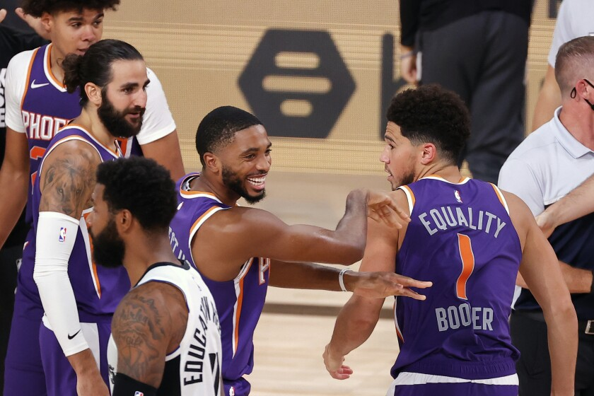 Phoenix Suns' Devin Booker (1) celebrates with teammate Mikal Bridges after scoring the game winning basket against the Los Angeles Clippers in an NBA basketball game Tuesday, Aug. 4, 2020, in Lake Buena Vista, Fla. (Kevin C. Cox/Pool Photo via AP)