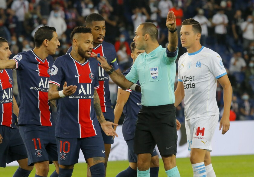 Referee Jerome Brisard waves away the appeals of PSG players for a penalty during the French League One soccer match between Paris Saint-Germain and Marseille at the Parc des Princes in Paris, France, Sunday, Sept.13, 2020. (AP Photo/Michel Euler)