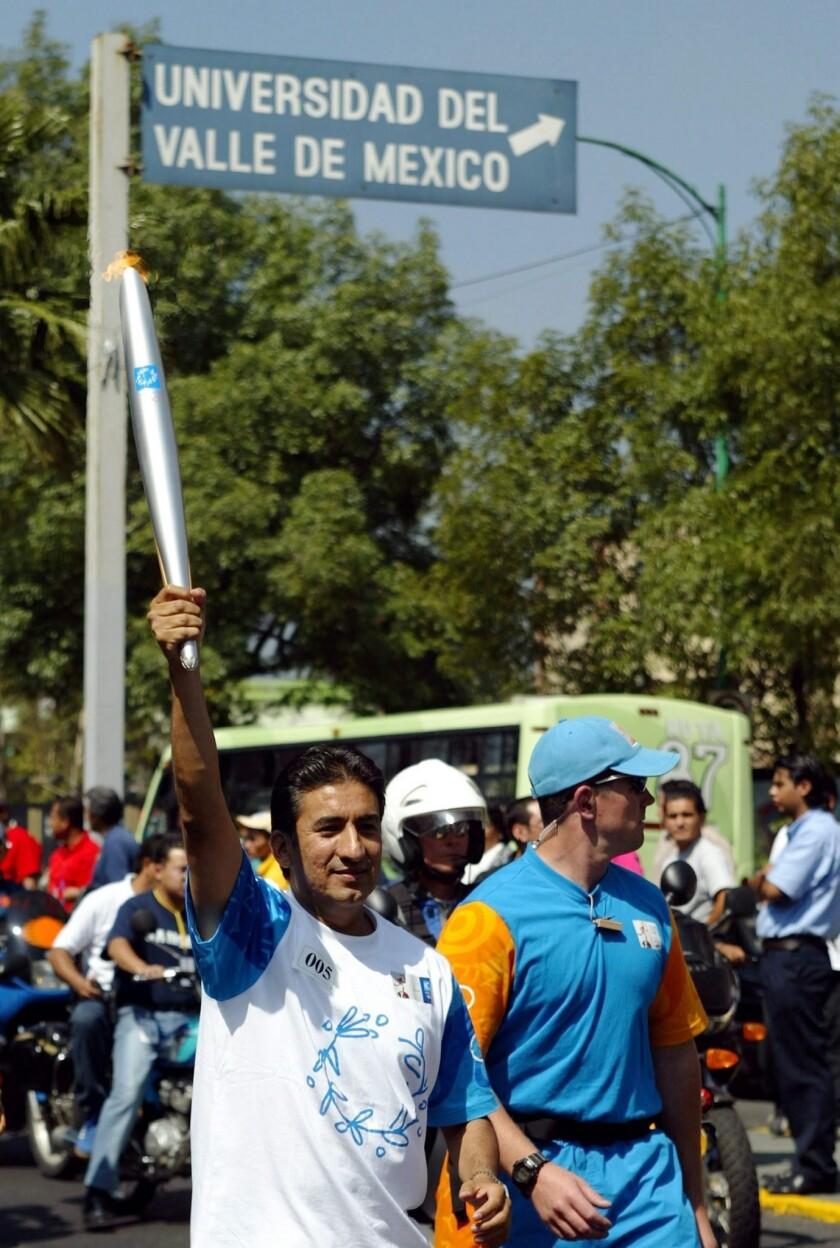 Ernesto Canto lleva la antocha olímpica.