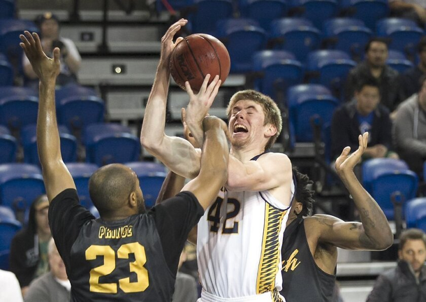 UC Irvine's Tommy Rutherford is fouled hard by Long Beach State's Roschon Prince.