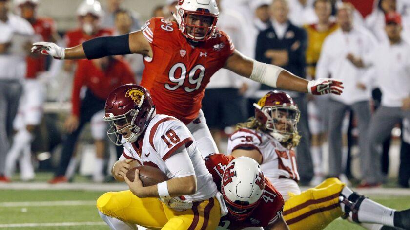 Utah defensive tackle Hauati Pututau (41) sacks USC quarterback JT Daniels (18) during the first half on Saturday in Salt Lake City.