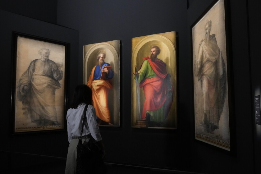 """A woman admires, from left, a black and white preparatory cartoon for the St. Peter painting, by Fra Bartolomeo, 1513, the oil on wood painting of St. Peter, by Raffaello, 1517-1518, the oil on wood painting of St. Paul, by Fra Bartolomeo, 1513, and it's black and white preparatory cartoon, by Fra Bartolomeo, 1513-1514, during a press preview of the """"St.Peter and St.Paul by Fra Bartolomeo and Raffaello"""" exhibition, at the Vatican Museums, at the Vatican, Friday, Sept. 24, 2021. The two restored paintings, started by Fra Bartolomeo and finished by Raffaello after his death, that have been kept in the Papal Apartments, unseen by the public for decades, and the two cartoons by Far Bartolomeo, coming from Forence's Uffizi Museum, will be on display from Sept. 25, 2021 to Jan. 9, 2022. (AP Photo/Andrew Medichini)"""