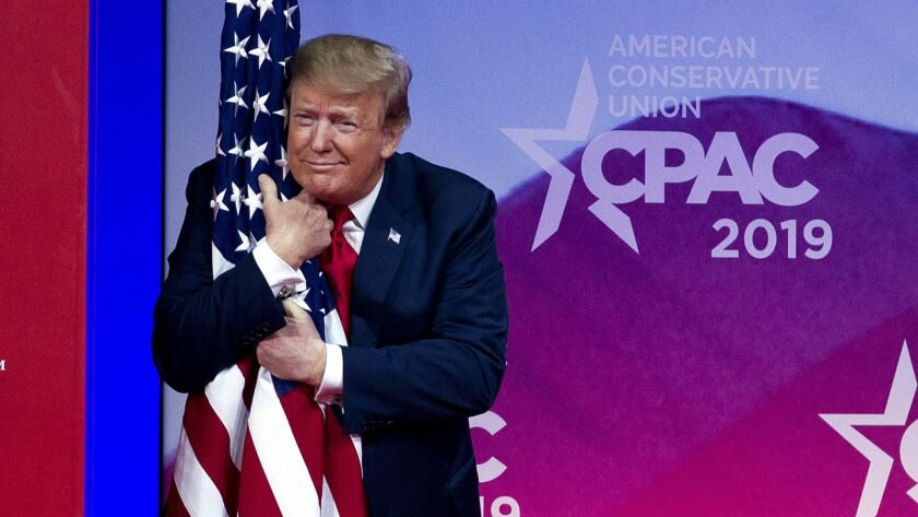 President Donald Trump hugs the American flag as he arrives to speak at Conservative Political Actio