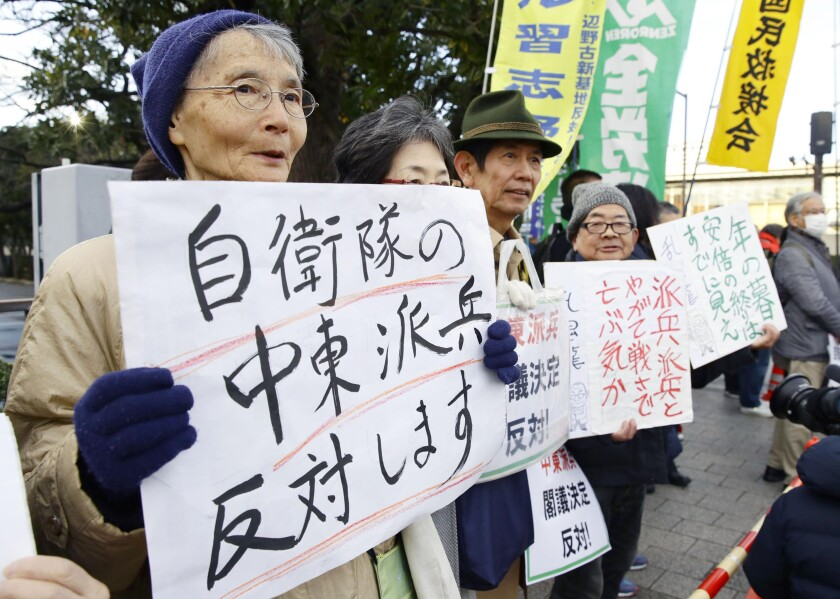 People opposed to Japan's planned troop dispatch display placards outside the official residence of Prime Minister Shinzo Abe in Tokyo on Friday.