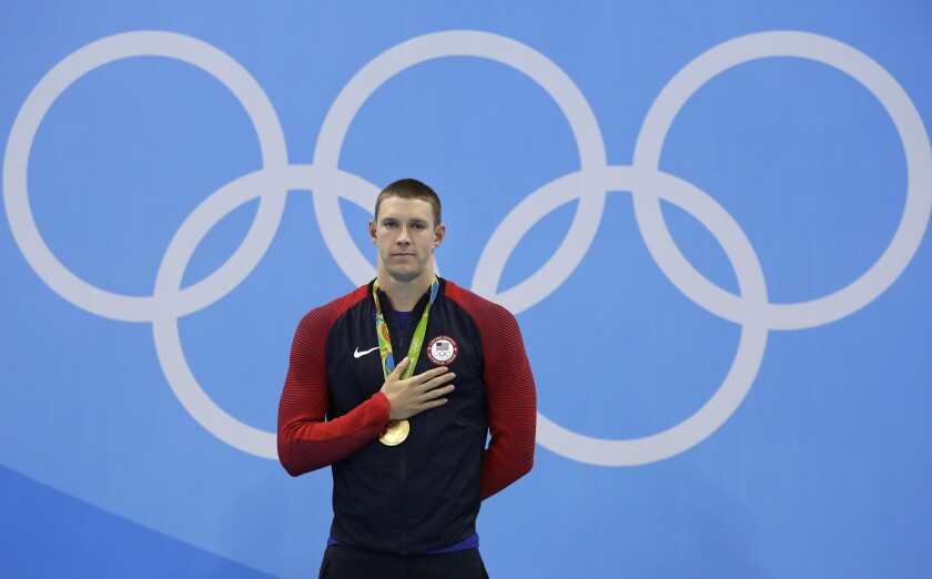 FILE - United States' gold medal winner Ryan Murphy listens to the anthem during the medal ceremony for the men's 200-meter backstroke final during the swimming competitions at the 2016 Summer Olympics in Rio de Janeiro, Brazil, in this Thursday, Aug. 11, 2016, file photo. The last time the American men lost a backstroke race at the Olympics, Ryan Murphy wasn't even born. It's likely up to him to keep the remarkable streak alive. (AP Photo/Michael Sohn, File)