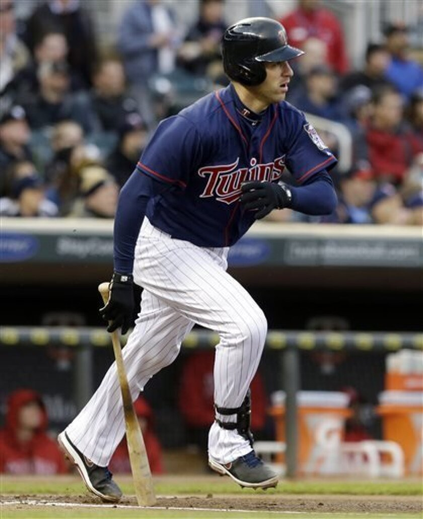 Minnesota Twins' Joe Mauer hits a single off Los Angeles Angels pitcher Jason Vargas in the first inning of a baseball game, Tuesday, April 16, 2013, in Minneapolis. (AP Photo/Jim Mone)