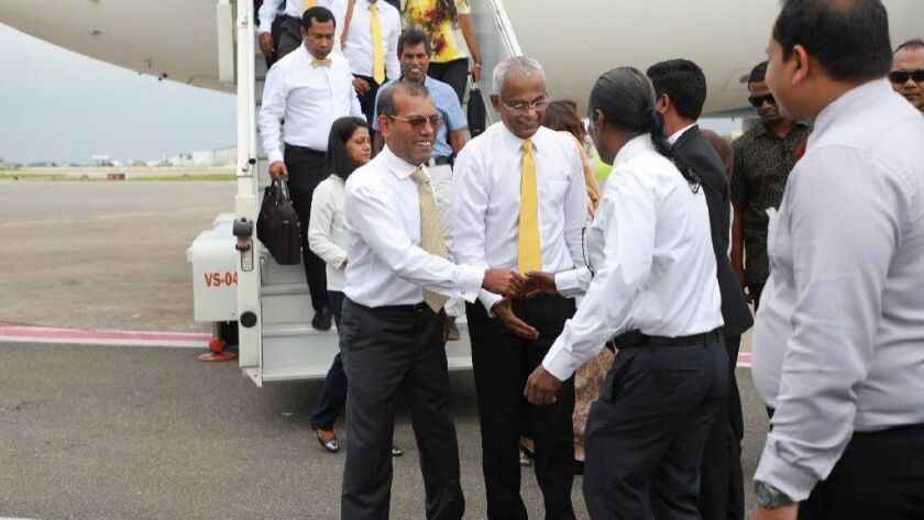 Former President Mohamed Nasheed, center left, is greeted by supporters upon returning to the Maldives, Nov. 1, 2018. To his left is President-elect Ibrahim Mohamed Solih.