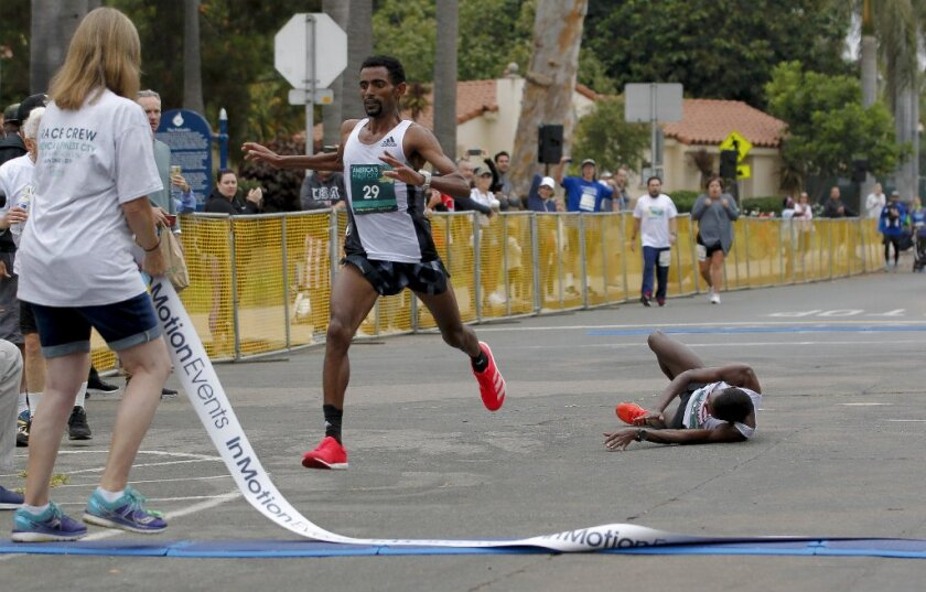 Daniel Mesfun of Eritrea crosses the finish line at the 42nd annual America's Finest City Half Marathon ahead of Kenya's Dominic Korir, who tripped with yards to go.