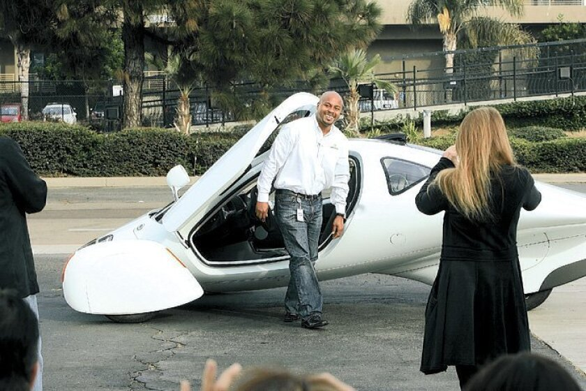 Marques McCammon, chief marketing officer of Aptera, showed the Aptera 2e electric car recently. Aptera yesterday pushed back its production schedule and said its first vehicles won't be ready till 2010.