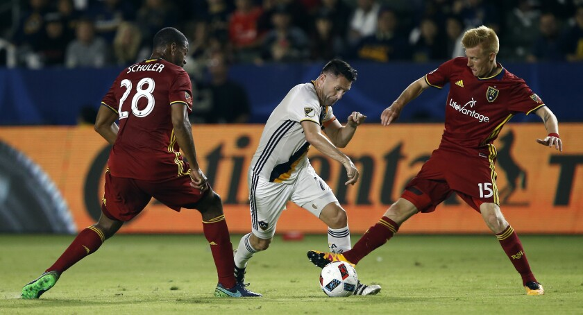 Galaxy forward Robbie Keane, center, tries to split between Real Salt Lake forward Chris Schuler and defender Justen Glad during the second half of a knockout-round MLS playoff match on Oct. 26.